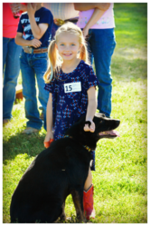 A cute little blonde girl with her medium sized black dog