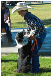 A boy in a cowboy hat leaning down to hug his black and white dog